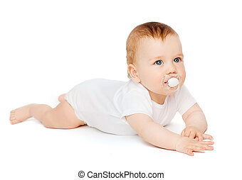 smiling baby lying on floor with dummy in mouth