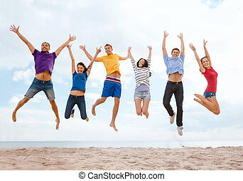 group of friends jumping on the beach - summer, holidays,...