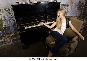 young blond girl playing on piano in ruined interior
