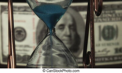 sandglass - hourglass on the background of dollar bills