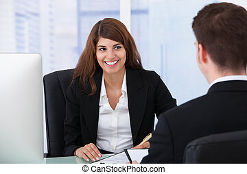 Businesswoman Interviewing Male Candidate At Desk - Happy...