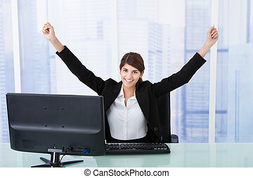 Businesswoman With Arms Raised At Computer Desk - Portrait...