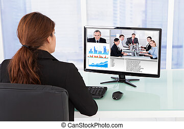 Businesswoman Video Conferencing With Team On Computer -...