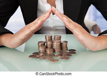 Businesswoman Sheltering Coins In House Shape
