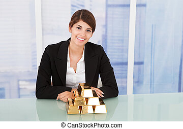 Confident Businesswoman Showing Stacked Gold Blocks On Desk...