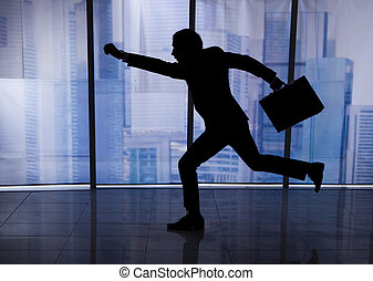 Businessman With Briefcase Running In Office - Full length...