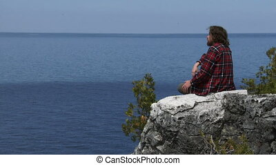 Hiker resting on a rock, contemplating the panorama of...