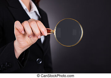Midsection Of Businesswoman Holding Magnifying Glass -...