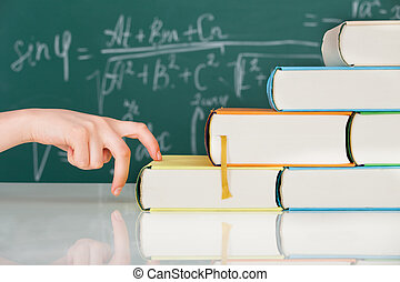 Hand Climbing Stack Books In Classroom - Cropped image of...
