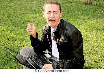 Crying boy with laptop on the grass.