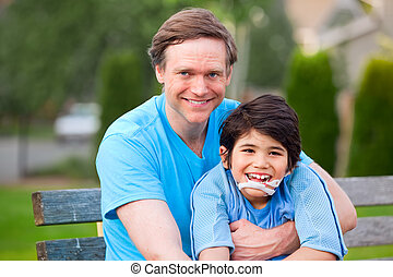 Handsome father holding smiling disabled son outdoors -...