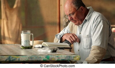 Senior reading book - Senior man, relaxing and reading a...