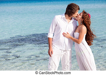 A couple is kissing on the beach