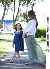 Mother and eight year old daughter in a summer park -...