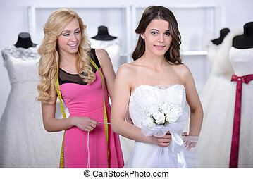Buying Wedding Dress - Smiling pretty bride chooses white...