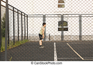 Boy on a sports ground view through fence