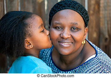 African girl kissing mother on cheek. - Close up portrait of...