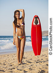 Surfer Girl - A beautiful girl at the beach posing with her...
