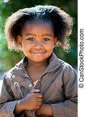 Cute african girl in brown jacket.