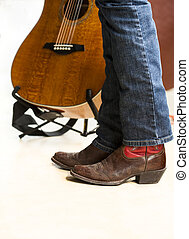 Country style - Legs of country musician in boots in front...