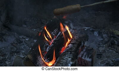 Veggie hot dog roasting on fire during camping