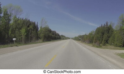 Camera car in Canadian countryside, road passing in the...