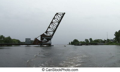 Lift bridge seen from river, with small boat passing...