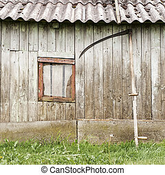 old wooden barn with broken window and scythe leaning...