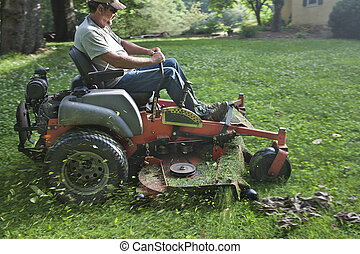 Landscaper on riding lawn mower - Landscaper cutting grass...