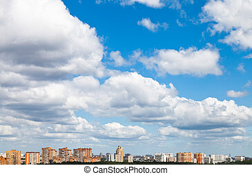 many woolpack clouds over city in summer day
