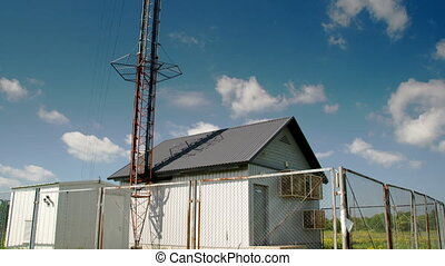 Tall cellular tower beside a small house - A tall cellular...