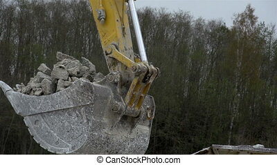 A backhoe s head with stones