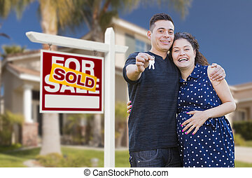 Hispanic Couple, Keys, New Home and Sold Real Estate Sign -...