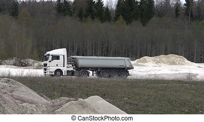 A big dump truck running inside the limestone mining...