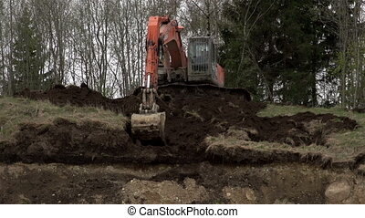A backhoe clearing off a land portion - A backhoe clearing...