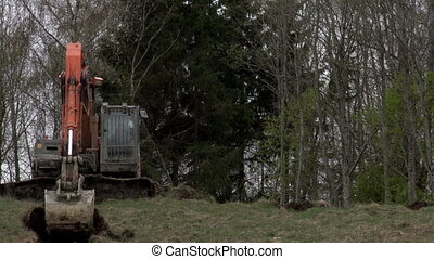 A backhoe getting off some land portion - A backhoe getting...