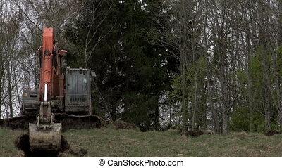 A backhoe getting off some land portion - A backhoe getting...