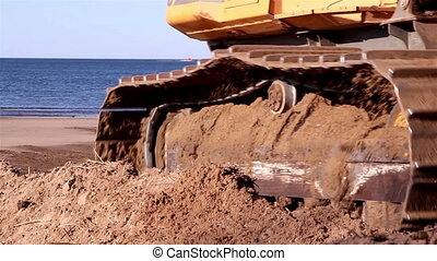 A bulldozer going back to get some soil near the beach
