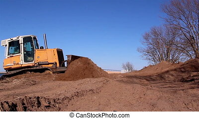 A yellow bulldozer grabbing some soil