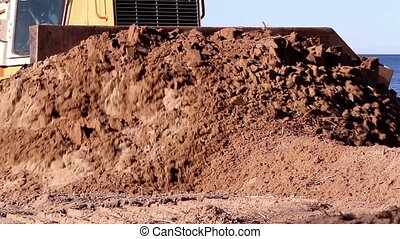 Brown soil being pushed by the bulldozer near the seashore