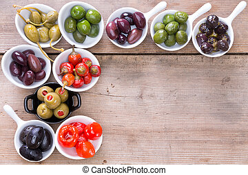 Border of olives and peppers on a wooden counter - Border of...
