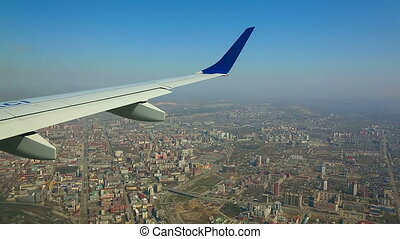 Flying over the city - View from the cabin porthole of an...