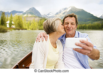 Senior couple on boat with mountains in background taking...