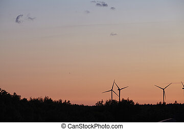 Beldorf - Wind power stations at the horizon on sunset -...