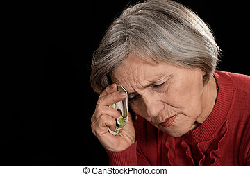 old woman in red crying on a black background