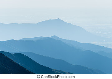 Mountain silhouette at sunrise - Telephoto view of distant...
