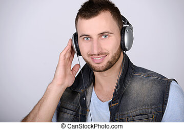 Music - Attractive guy holding headphones listening to music