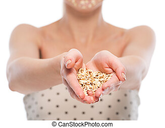 Closeup on young woman with oatmeal facial mask showing...