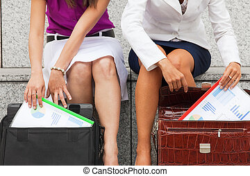 businesswomen with budget reports - two business women...