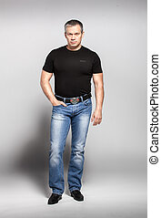 Adult man in black t-shirt and jeans posing in studio -...